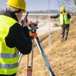 Geodesist measure land with tacheometer highway — Stock Photo