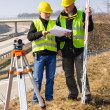 Stock Photo: Geodesist read plans on construction site