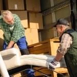 twee verhuizer belasting van met meubilair dozen — Stockfoto