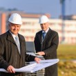 Two architects at construction site review plans — Stock Photo