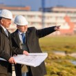 Two architects man point at construction site - Stock Photo