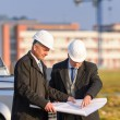 Two architects man look at construction plan — Stockfoto