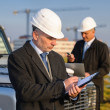Architect man make notes on construction site - Stock Photo