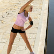 Fit woman stretch body by water pier — Stock Photo