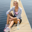 Young sport woman relax on pier lake — Stock Photo #10515854