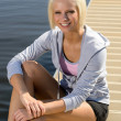 Young sport woman relax on pier water — Stock Photo