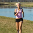 Young woman jogging river park sunny day — Stock Photo #10515892