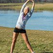 Stock Photo: Young woman stretching outdoors before jogging