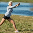 Young woman stretching outdoors before jogging — Stock Photo #10515906