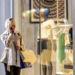 Young woman window shopping evening city — Stock Photo
