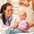 Pediatrician examine baby with stethoscope - Stock Photo