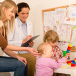Pediatrician female observe children play activity - Stock Photo