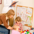 Pediatrician female review children play activity — Stock Photo