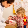 Pediatrician give lolly to little child girl — Stock Photo