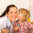 Pediatrician woman get kiss from child girl — Foto Stock