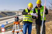 Geodesist 读取在建筑工地上的计划 — 图库照片