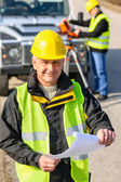 Land geodesist man hold plan reflective vest — Stock Photo