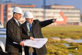 Two architects man point at construction site — Stock Photo