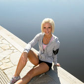 Sport woman relax on pier sitting water — Stock Photo