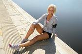 Donna sportiva rilassarvi sul molo di lago — Foto Stock