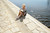 Sport woman relax on pier looking water — Stock Photo