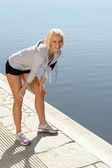 Sportovní žena strečink nohy na dok — Stock fotografie