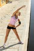 Fit woman stretch body by water pier — Photo