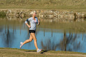 Running woman outdoor sport by river bank — Stock Photo