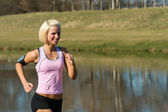 Young woman jogging lake park sunny day — Stock Photo