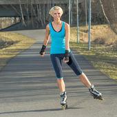 Kvinna rullskridskoåkning i park leende sommaren — Stockfoto