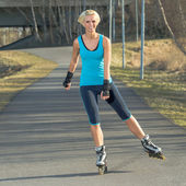 Woman roller skating in park smiling summer — Stock fotografie