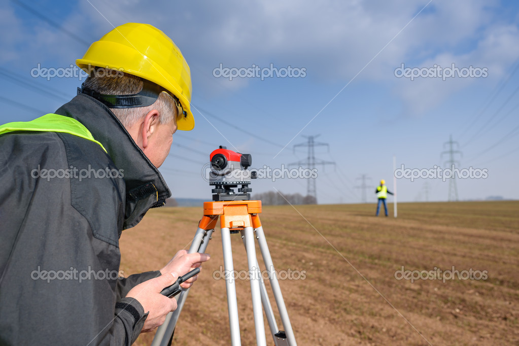 Land surveyors measuring with tacheometer speaking through transmitter — Stock Photo #10515233