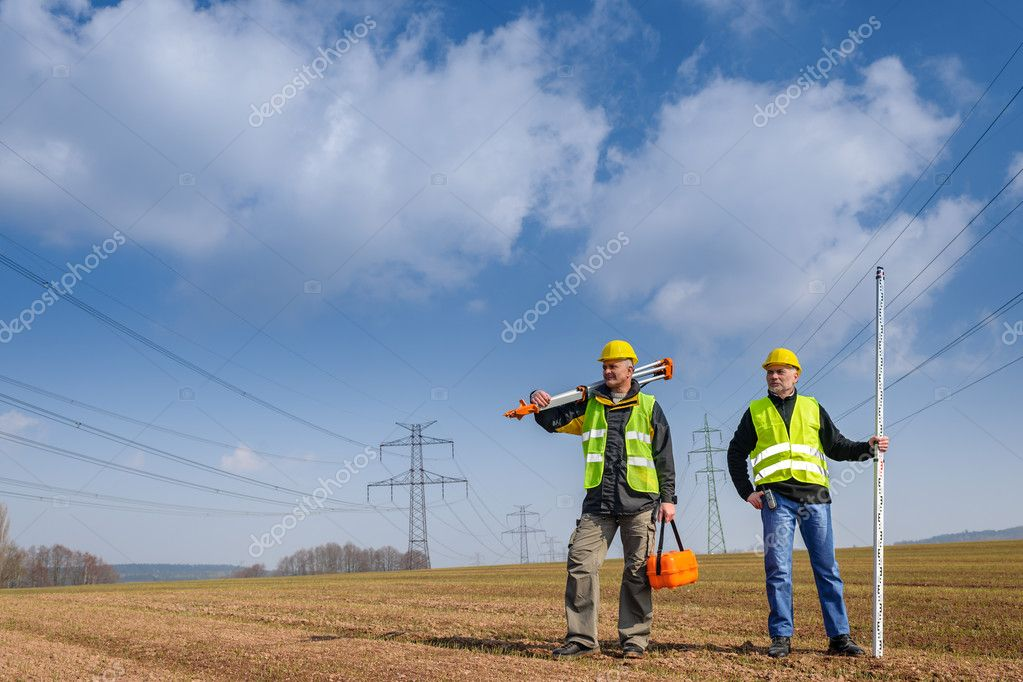 Portrait of two geodesist holding measuring equipment on construction site — Stock Photo #10515236