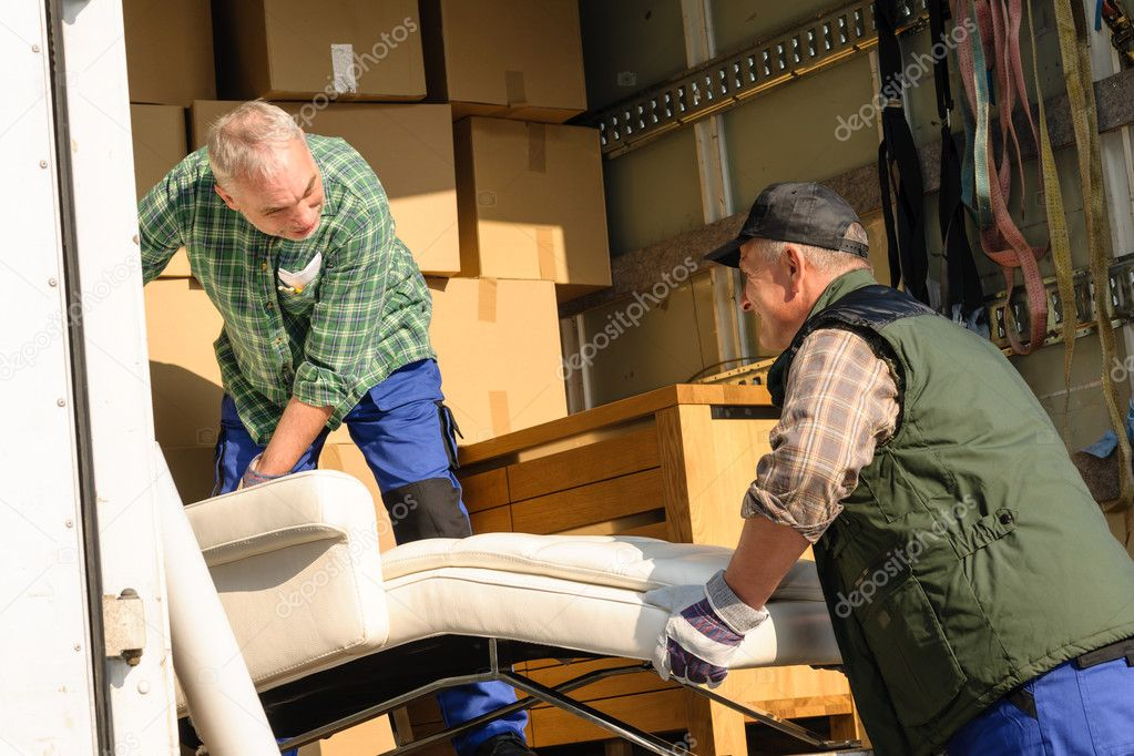 Two male movers putting furniture and boxes  in moving truck — Stock Photo #10515260