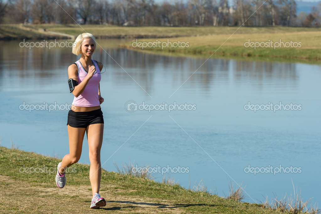 Young woman jogging recreational running by river sunny day — Stock Photo #10515882