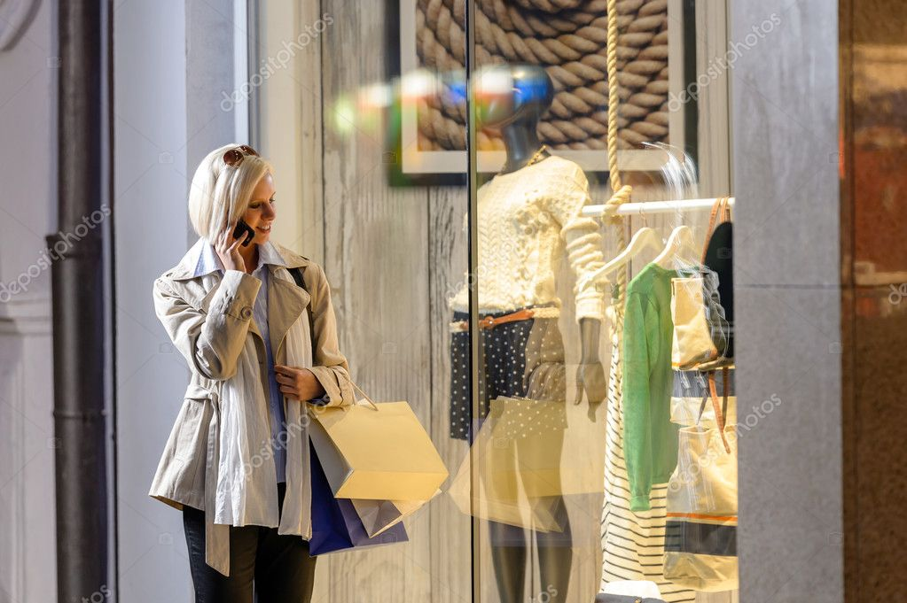 Young woman shopping evening city looking into shop windows phone — Stock Photo #10515926