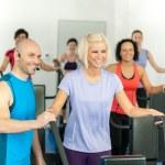 Fitness instructor leading gym exercise — Stock Photo