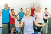 Fitness young group on elliptical cross trainer — Stock Photo