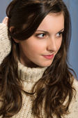 Brunette woman in beige sweater looking aside — Stock Photo