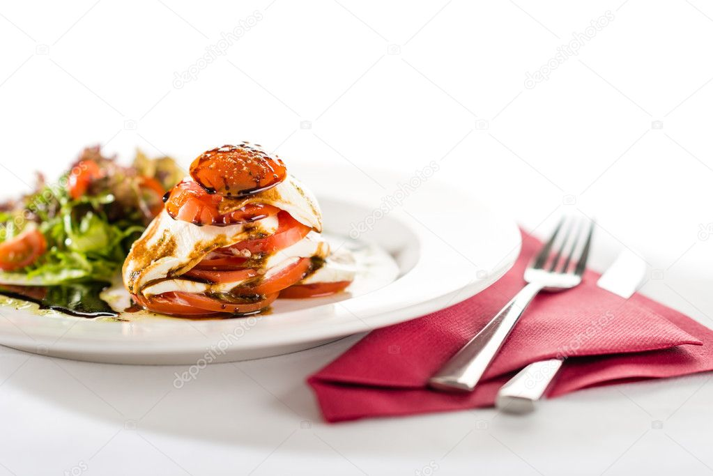 Fresh and delicious Caprese salad with tomatoes isolated on white — Stock Photo #10724857
