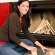 Home fireplace woman put logs happy winter - Foto de Stock