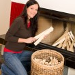 Home fireplace woman put logs happy winter - Foto Stock