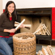 Home fireplace woman put logs happy winter - Stockfoto