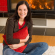 Home fireplace happy woman hold cushion - Stock Photo