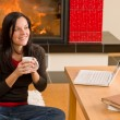 Home living woman with laptop by fireplace — Stock Photo