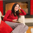 Fireplace woman with phone lying home sofa — Stok fotoğraf