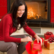 Christmas wrap present happy woman home fireplace — Stock Photo #8037818