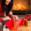 Christmas wrap present happy woman home fireplace — Stock Photo