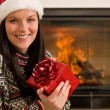 Christmas present woman Santa hat home fireplace — Stockfoto