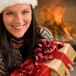 Christmas present woman Santa hat home fireplace - Stock Photo